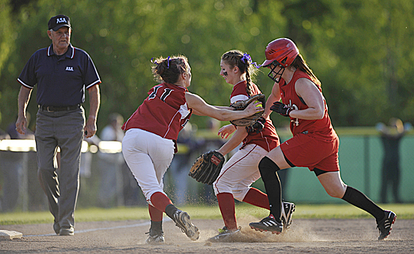 Dexter High School third baseman Jordyn Bell (11, left) and teammate Kirstie Mower, center,  put the squeeze Central High School's Roberta Trafton, right, before she can get to third base in the first inning of their Class C  Eastern Maine final at Coffin field in Brewer Wednesday evening, June 15, 2011.
