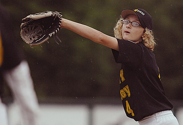 Kes Lavoie of Bangor stretches to catch a ball during warmups before her team's Bangor East Little League baseball game at Taylor Field on Friday night. Lavoie plays for Varney's, and she played baseball for Cohen Middle School this spring as well.