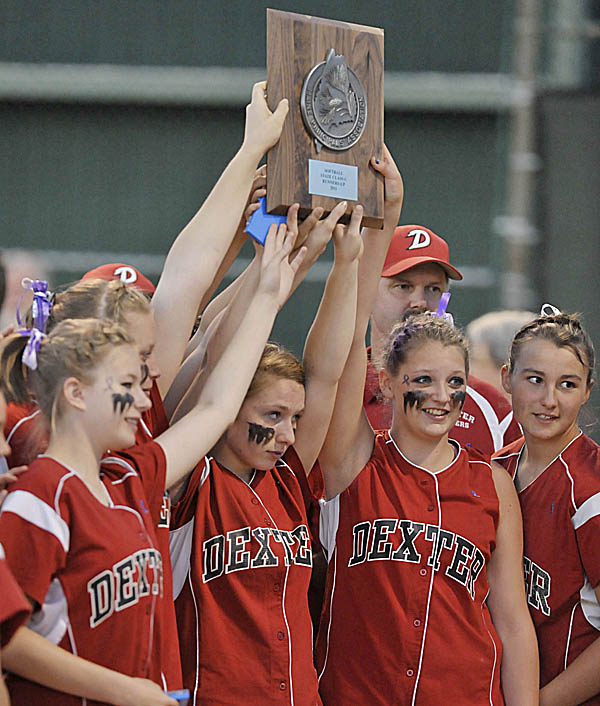 Dexter's softball team gather around their runnerup trophy Monday night after losing to Telstar High School in Brewer Monday, June 20, 2011.