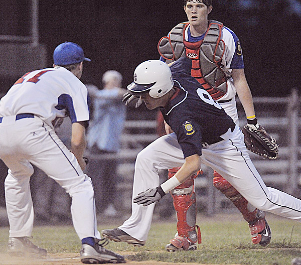 Casey Estes (left) of Motor City of Bangor prepares to tag Bangor's Nic Cota at home plate in the fifth inning of Thursday night's American Legion baseball game at Mansfield Stadium in Bangor. Motor City catcher Tyler Eddy looks on. Bangor defeated Motor City 7-1.