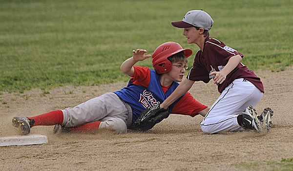 Lincoln's Logan Thompson, right, tags out Orrington's Gavin Matthieu as he tries to steal second base during the first inning of a District 3 Little League all-star game for ages 11-12 Tuesday. Lincoln won 3-0.