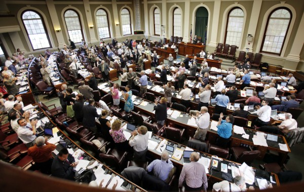 In this June 9, 2011 photo, legislators stand and applaud in the House chamber at the State House in Augusta. The state's first Republican-led Legislature in decades did as it promised as it rolled back business regulations, and after years of trying, made major changes in the health insurance laws during the six-month 2011 session.