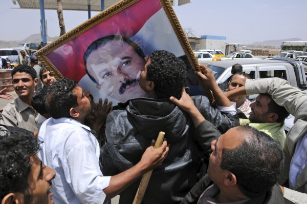 Supporters of Yemeni President Ali Abdullah Saleh kiss his portrait as they celebrate news that Saleh's health is stable, after being taken to Saudi Arabia to receive medical treatment for wounds he suffered in a rocket attack on his compound, in Sanaa, Yemen, Thursday, June 9, 2011. Government troops trying to recapture areas held by Islamic militants have killed 12 suspected al-Qaida members in the troubled southern province of Abyan, the Defense Ministry said Thursday.
