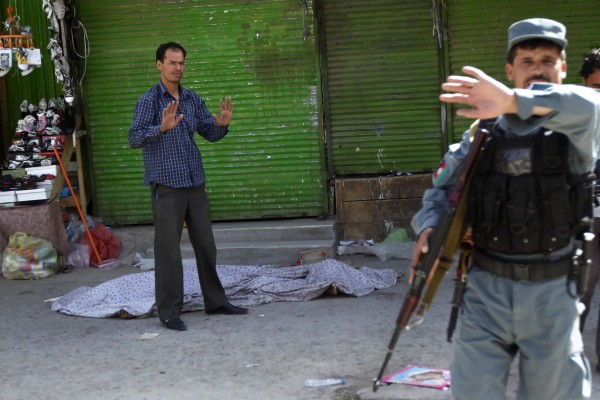 A police officer signals photographers to move away as another gestures as he stands next to the body of an alleged attacker in Kabul, Afghanistan, Saturday, June 18, 2011. Men dressed in Afghan army uniforms stormed the police station near the presidential palace and opened fire on officers, an eyewitness said. The Interior Ministry said in a statement that one of the attackers detonated a suicide bomb vest outside the gates while the others rushed in and began shooting.