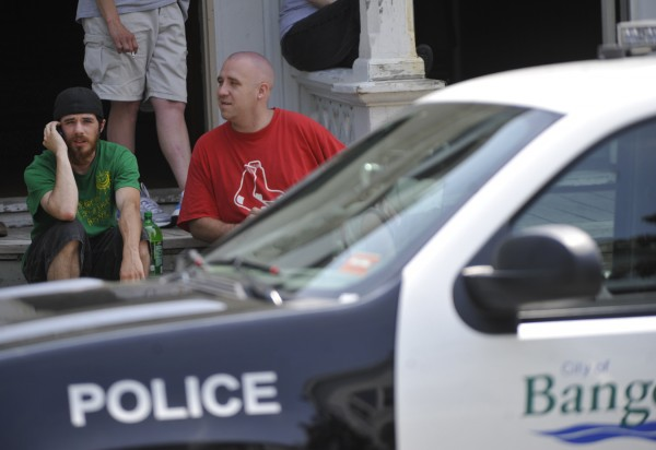 Waiting for police to allow him and friend Anthony Walton (right) back into Walton's apartment, Rick Coleman (left), 22, talked on his cellphone Thursday morning. Police are investigating a suspicious death in Bangor. Bangor Police Department's evidence response team was dispatched to 94-96 Fourth St. and gathered evidence in the apartment building's driveway as part of the investigation. Coleman said he he was staying at Walton's appartment overnight and got up early Thursday morning and saw a dead body in the driveway of his friend's apartment.