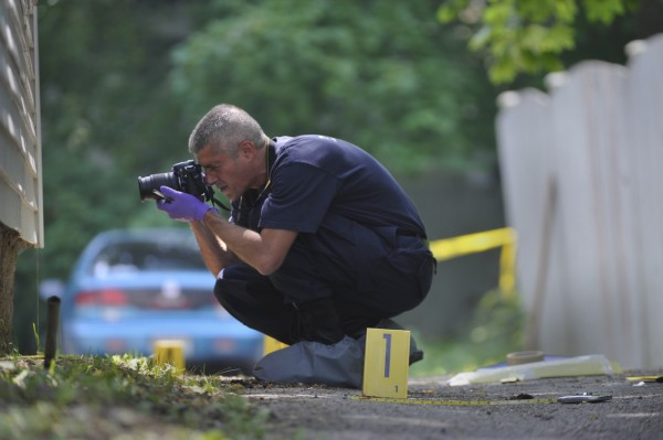 Bangor Police evidence technician Sgt. Paul Edwards takes pictures of the siding on an apartment buidling on 94-96 Fourth Street in Bangor as part of the police investigation into a suspicious death that occurred there earlier Thursday morning, June 9, 2011.