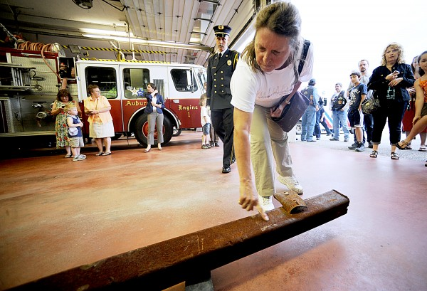 Alfreda Fournier of Auburn reaches down to touch a piece of twisted steel from the World Trade Center that was delivered to Auburn's Central Fire Station on Thursday evening. &quotI think it brings back the possibility of evil in this world and reminds us to respect our military,&quot Fournier said, &quotbecause as we're living here safe at home, they are fighting for our freedoms.&quot For a video of the delivery, please visit www.sunjournal.com.
