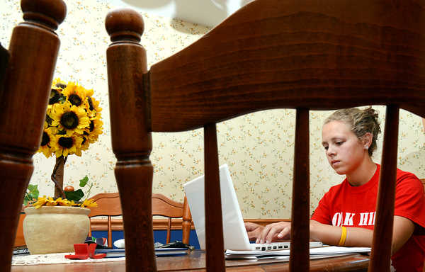 Darby Beaulieu, a senior at Oak Hill High School, uses her school laptop to write emails at her kitchen table in her Litchfield home Monday afternoon.