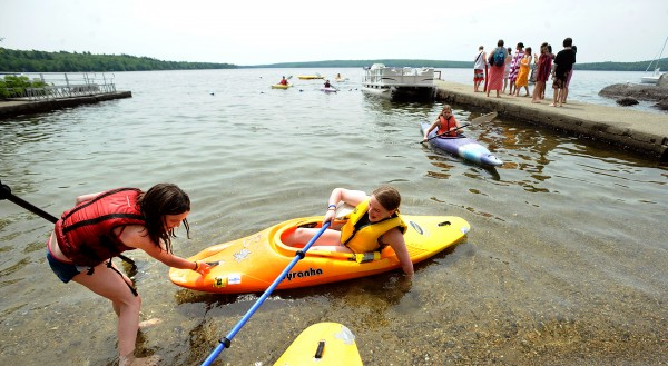 Aebie Blauvelt, 11, of Rumford gives Margo Roberts, 12, of Bangor a hand with landing her kayak after a morning outing on Branch Lake at Camp Rainbow in Ellsworth on Tuesday. They were among the 45 people who attend Camp Rainbow that provides a free week-long summer camp for children diagnosed with cancer and their families.  This is the 24th annual camp that is offered by the American Cancer Society.