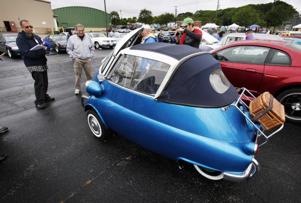 "Portland police chief James Craig (far left) judges a 1958 BMW Isetta during the ""Calling All Cars,"" car show Saturday, June 25, 2011, in Portland.  Craig was inspired to establish the ""Calling All Cars"" car show as a way to reach out to people in Portland. Craig is a car aficionado who owns a 1970 Pontiac GTO and a 2007 Corvette Z06."
