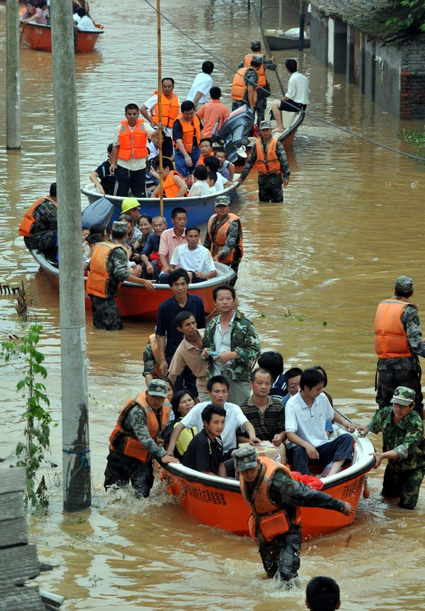 In this June 23, 2010 file photo released by China's Xinhua News Agency, armed police help residents evacuating from flooded area in Fuzhou city, central China's Jiangxi Province. More than 42 million people were forced to flee their homes because of natural disasters around the world in 2010, more than double the number during the previous year, experts said Monday, June 6, 2011.