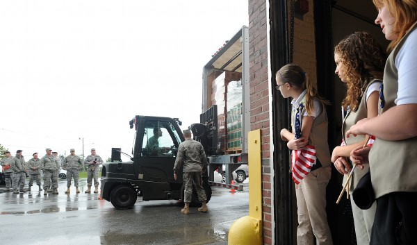 Members of Girl Scout Troop 650 from Pittsfield and soldiers watch as Girl Scout Cookies are unloaded at the Maine Air National Guard Base in Bangor on Tuesday afternoon, June 14, 2011. The 44,000 boxes of cookies will be distributed among the guard and reserve units in Maine. The Girl Scouts throughout Maine raised money for about 40 percent of the cookies and the rest was donated by ABC Cookies, the company that produces the sweets for the Girl Scouts.