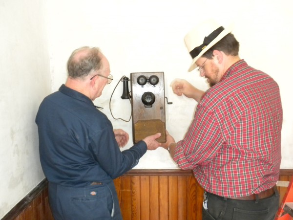 David Thompson, left, phone enthusiast and treasurer for the New England Museum of Telephoney, Inc., and Curran Homestead Living History Farm and Museum director Bruce Bowden install a new crank wall-mounted telephone Thursday, June 30, 2011. The historic crank phone will be installed in the kitchen of the old farm and another similar crank phone will be put up in the barn for visitors to use.