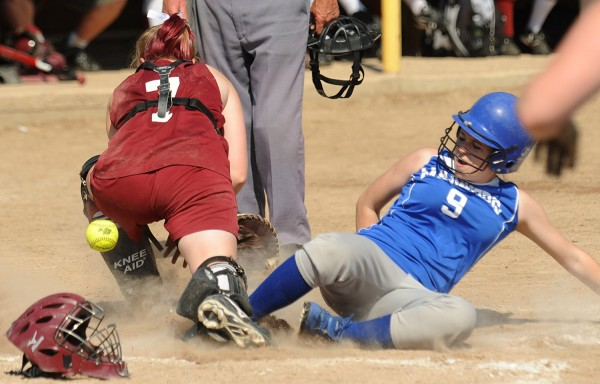 Deer Isle-Stonington High School's Emily Cormier (9) slides to home plate as Richmond Regional High School's Lindsy Hoppingarner fails to catch the ball during the fifth inning of the Class D State Softball Championship game in Standish Saturday. Deer Isle-Stonington High School won the game 7-2.