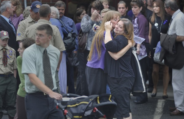 Friends and family gather outside Dexter Regional High School following Saturday morning's funerals for Amy Lake and her two children Monica, 12, and Coty, 13. Several hundred mourners attended the funeral in an outpouring of support for the family as well as to heighten awareness about domestic violence.