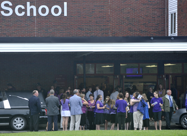 Friends and family gather outside Dexter Regional High School following Saturday morning's funerals for Amy Lake and her two children Monica,12 and Coty, 13. Several hundred mourners attended the funeral in an outpouring of support for the family as well as to heighten awareness against domestic violence.