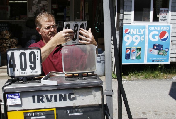 Convenience store owner Floyd Bisson, lowers the price of regular gas at the pumps in front of his store in Phippsburg on Monday, June 27, 2011. The nationwide average for retail gasoline fell to $3.57 per gallon Monday according to AAA, Wright Express and the Oil Price Information Service. Prices have dropped 24 cents in a month.