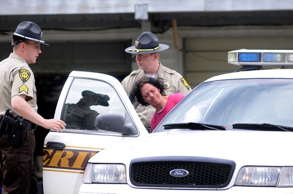Sgt. William Birch (left) and Chief Deputy Troy Morton, both of the Penobscot County Sheriffs Dept., help Torianne Barrett into a sherriffs car as they prepare to take her for a medical evaluation following a report of a home invasion at the Eddington residence of Barrett and her husband Abram Barrett Thursday morning, June 2, 2011.
