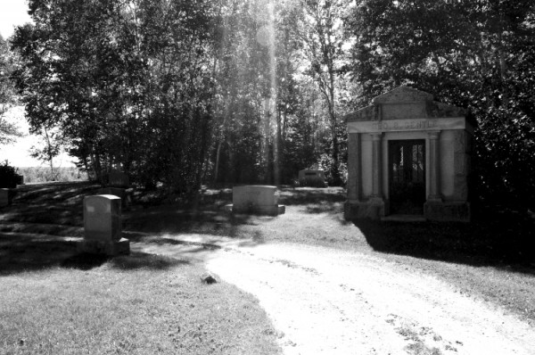 Sunlight streams through trees next to a mausoleum in Evergreen Cemetery in Houlton. Jason Grass, a Fort Fairfield artist, has created a 162 page photography art table book entitled Faded Away, which depicts images from eight cemeteries in Aroostook County. He will host a book signing at the University of Maine at Presque Isle on June 17.
