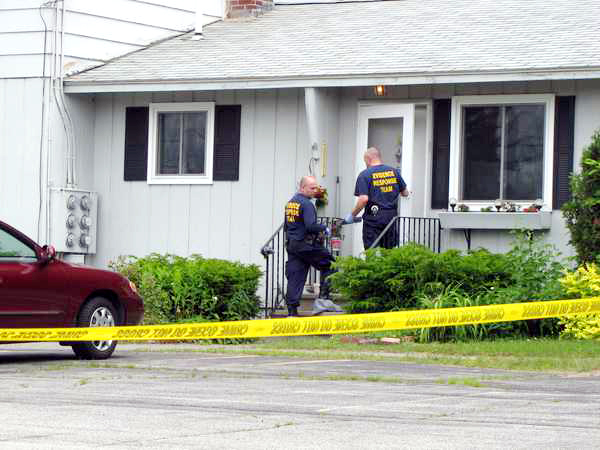 State Police investigators enter the Farmington home of Grace Burton at 195 Fairbanks Road, Apt. 5,  Tuesday. Burton, 81, was killed during a home invasion early Tuesday morning, June 21, 2011.
