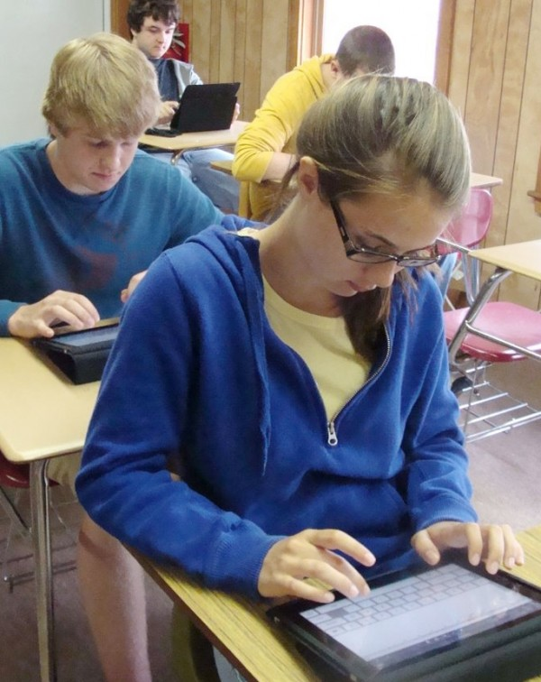 Foxcroft Academy students, including Emily Higgins (front) and Cooper Marden, both freshmen, finish up a pilot project using iPads in the classroom Thursday. The project, which involved the use of about 60 iPads that were shared among the students and staff was so successful that the academy is purchasing iPads for all students for use next year.