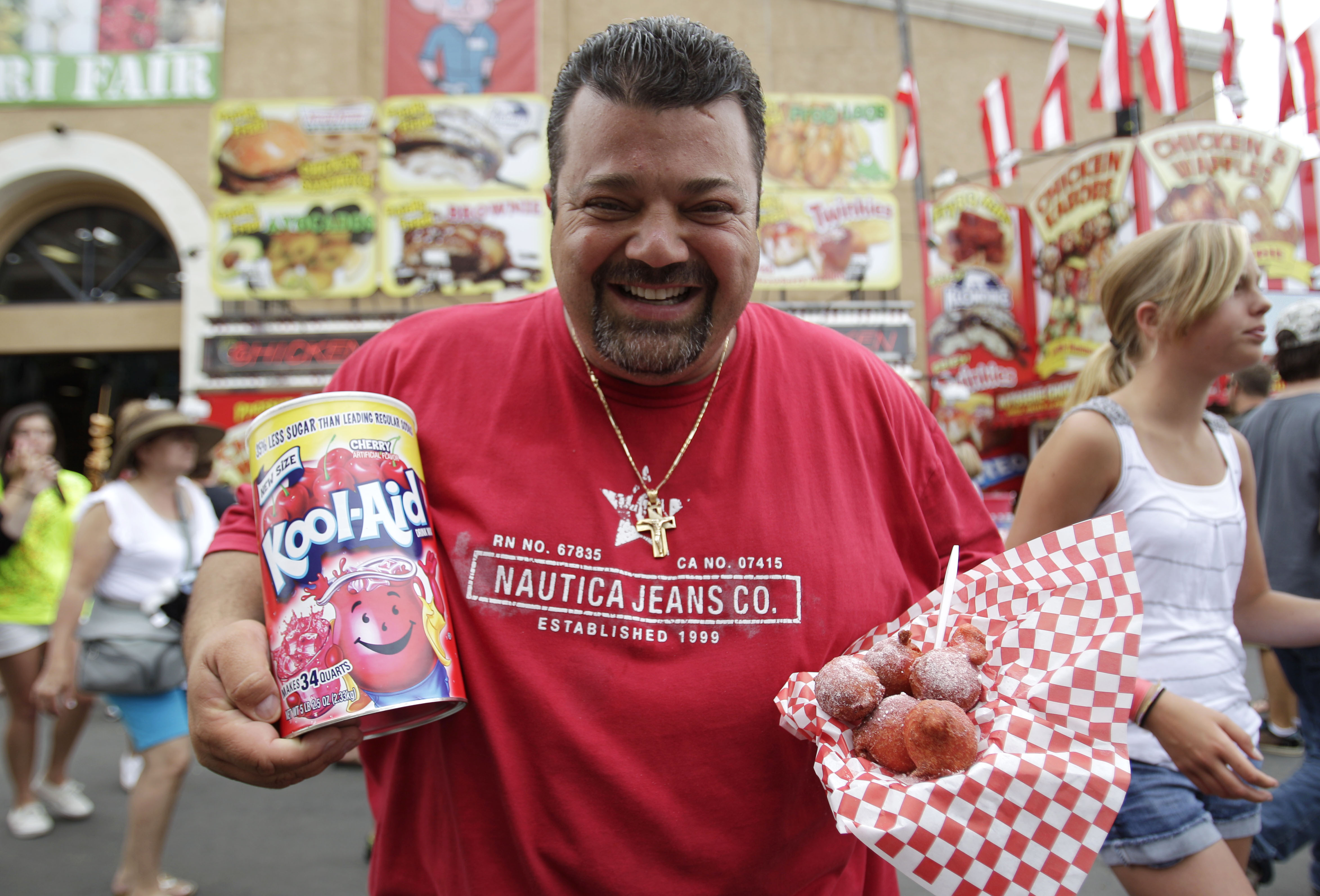 "Charlie Boghosian, known as, ""Chicken Charlie,"" poses holding Kool-Aid and his fried Kool-Aid balls at the San Diego County Fair on Wednesday, June 22, 2011, in Del Mar, Calif.  Boghosian's fried confections have been a popular addition to his menu this year, which includes fried Klondike bars, Girl Scout cookies, and Twinkies."