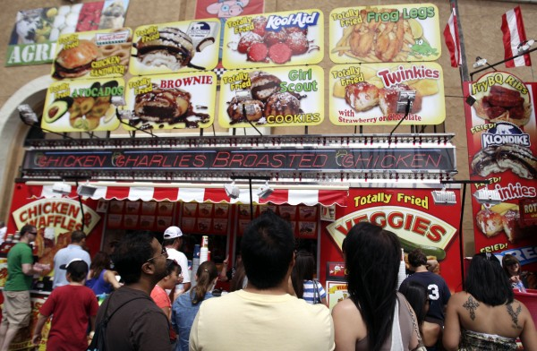 People look at an overhead menu featuring  fried Kool-Aid ball at the San Diego County Fair on Tuesday, June 21, 2011, in Del Mar, Calif. The crispy balls with their red-hot insides are a big seller at the fair this year.