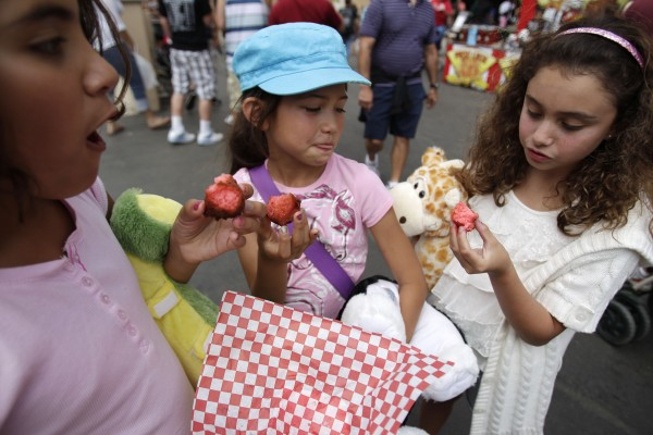 Three girls who declined to give their names try fried Kool-Aid balls at the San Diego County Fair on Tuesday, June 21, 2011, in Del Mar, Calif. The crispy balls with their red-hot insides are a big seller at the fair this year.