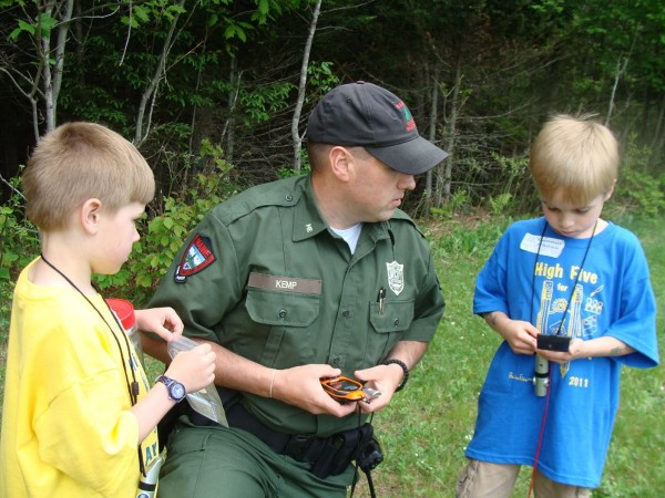 Arts Alive Day was celebrated Friday at the Piscataquis Community Elementary School in Guilford. Among those who volunteered their time during the event was Game Warden Jeremy Kemp of the Department of Inland Fisheries and Wildife who worked with children on geocaching and who instructed students on what to do if they got lost. Here, he and student Dean Demmer (left) observe Connor Chase use a GPS device.