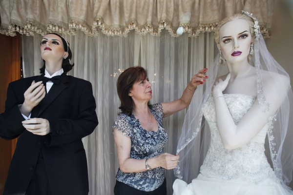 Carmela Kenney arranges a bridal veil for a same-sex pair of mannequins in the window of Sposabella Couture, Monday, June 27, 2011 in Brooklyn, N.Y.  New York businesses that cater to the wedding and honeymoon trade are hoping for an economic jolt from the passage of the same-sex marriage law.