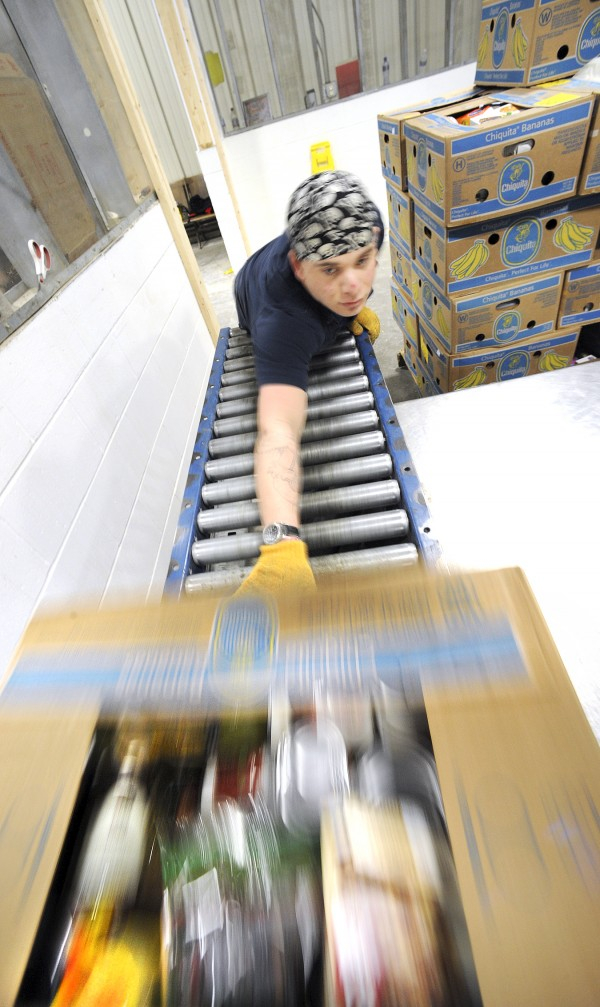 Derek Sluhoeki of Greene rolls boxes down a conveyor belt to be sorted at the Good Shepherd Food Bank in Auburn. Since its inception, the process of handling the massive volume of items has become more streamlined, and more innovations are on the way to help deliver the donated goods.