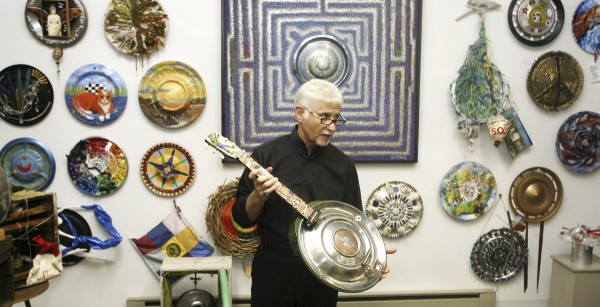 Ken Marquis, founder of the Landfillart Project, holds an art piece made into a six-string musical instrument Tuesday, May 24, 2011, while among some of more than 800 pieces made using hubcaps he has on display at his art gallery in Wilkes-Barre, Pa.