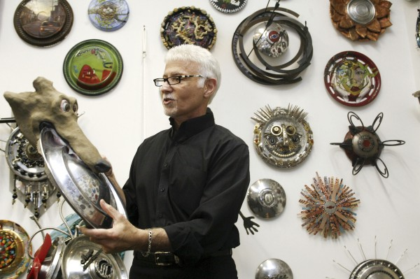 "Ken Marquis, founder of the Landfillart Project, holds an art piece called ""Frisbee"" on Tuesday, May 24, 2011, while among some of more than 800 pieces made using hubcaps he has on display at his art gallery in Wilkes-Barre, Pa."