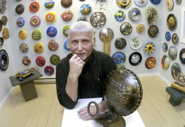 Ken Marquis, founder of the Landfillart Project, stands in one of the three areas of his Wilkes-Barre, Pa., art gallery Tuesday, May 24, 2011, among some of the 800-plus hubcaps he has been sent from artists in 52 different countries.