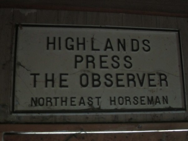 An old sign in the rafters for the Highlands Press Print Shop.