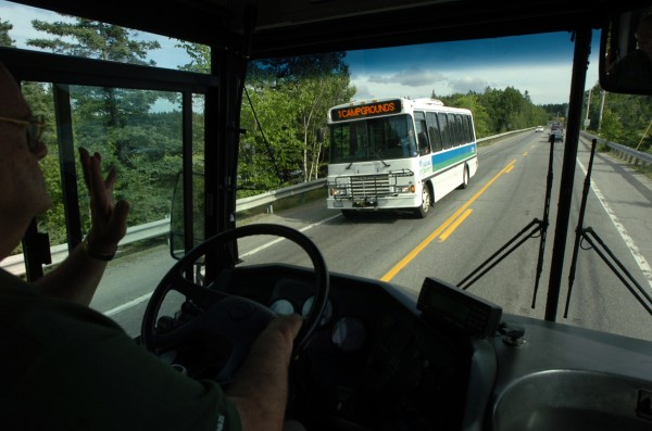 Island Explorer bus driver Galen Ireland waves to a fellow explorer bus driver as the two pass while covering the campground in Trenton to the Village Green in Bar Harbor.