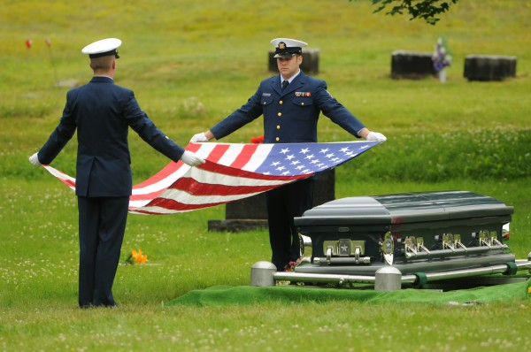 Coast Guard Honor Guard members, Scott Nickles (left) and Daniel Harn (right) fold an American flag that was drapped over the casket containig the remains of Richard Jeskey during his funeral at Riverview Cemetary in Bucksport on Saturday, June 25, 2011.