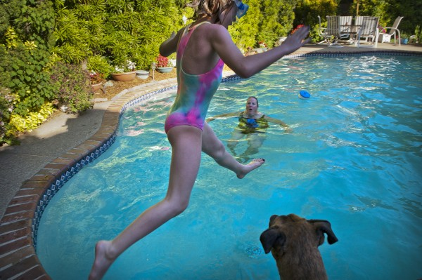 "At home in Carmichael, Calif., ""Grandma Cheryll"" Moore enjoys the pool and keeps an eye out for Mya Honsvick, 10, to make a splash as Kuda, the family dog, watches. This fall, Mya will cheer on her energetic grandmother in a triathlon."