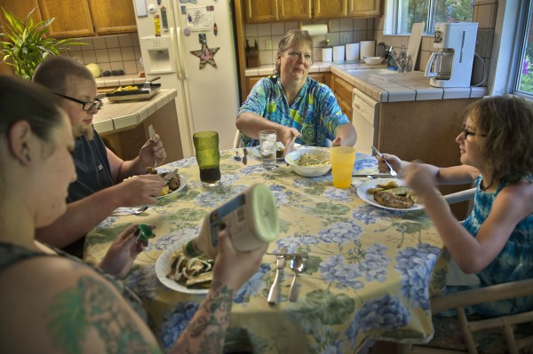 The multigenerational, blended Moore family has dinner together in their Carmichael, Calif. home. Cheryll Moore, 55 (center) is joined by son, Sean, and daughter-in-law, Beth Moore (left), and Beth's 10-year-old daughter, Mya Honsvick (right).