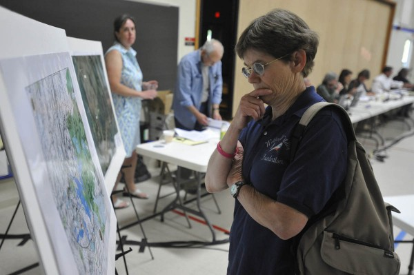 "Linda M. Ilse, a research assistant professor of wildlife ecology at the University of Maine in Orono, looks over a project map for the proposed Bowers wind turbine project in Carroll Plantation and Kossuth Township Maine before LURC's public hearing Monday evening, June 27, 2011 at Ella P. Burr School in Lincoln. "" I'm in favor of wind power, but not in the way this is being done, particularly with regard ot siting,"" said Ilse before the start of Monday's hearing. ""I'm concerned about the impacts on the landscape and on wildlife. I'd like to see more research done prior to siting, Ilse added."""