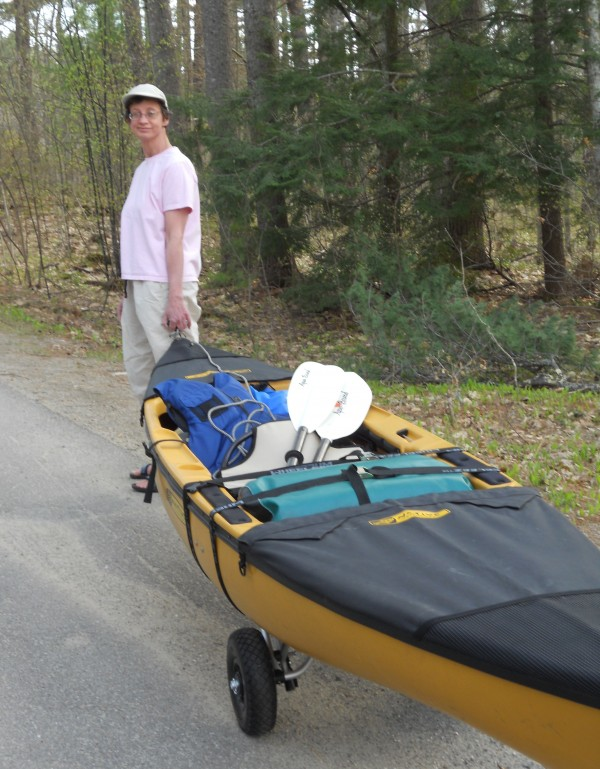 Laurie Chandler and her fully loaded kayak. The trip requires several extended portages of her efficiently loaded kayak. Bears don't worry her–but skunks do, she says with a chuckle. Image: Katie Gormley