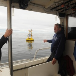 Peter Jumars, the director of School of Marine Sciences at the University of Maine, talks about an observation buoy at the future site of an offshore wind energy test turbine about two miles south of Monhegan Island during a tour of the area Monday. On the left is Dr. Christopher Hart of the U.S. Department of Energy on the right is Peter Browne of HDR Enigineering.