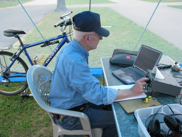 Amateur radio operator Norm Clanton of Newry listens for a Morse code response to his call sign Saturday during the nation's ham radio Field Day. It is a 24-hour contest designed to encourage ham operators to set up their equipment in a temporary location to develop their emergency communication skills. Clanton uses the bicycle in the background and a treadmill motor to generate power for his radio.