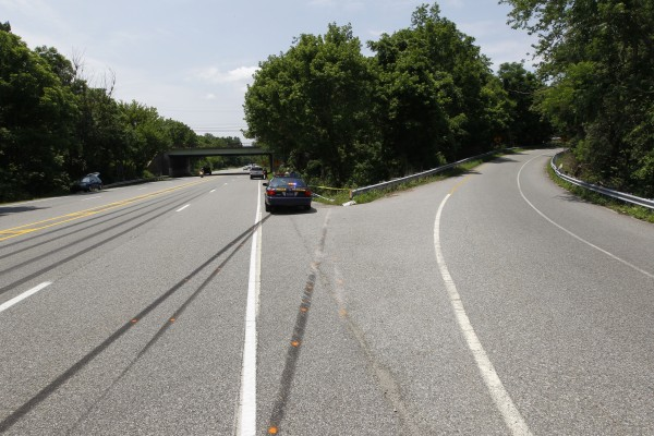 A police car sits near skid marks leading to the scene of an auto accident Monday, June 20, 2011, in West Chester, Pa. West Goshen Township police say Jackass cast member RyanDunn and a passenger died after his car left the roadway and burst into flames.