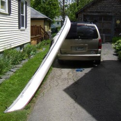 After placing blanket over rear edge of vehicle, lift bow onto back of vehicle behind roof racks.