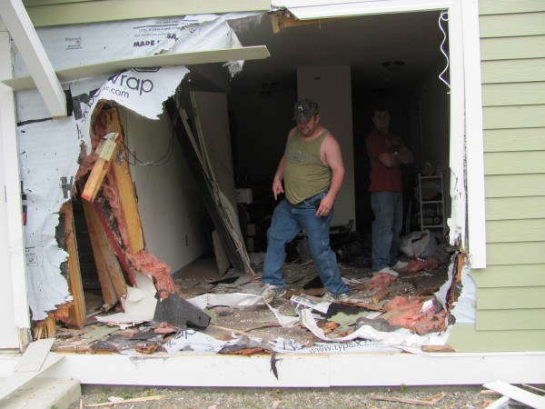 Joseph Sanborn steps over wreckage in his living room on Friday after a car crashed through the wall at 104 Somerset Ave.