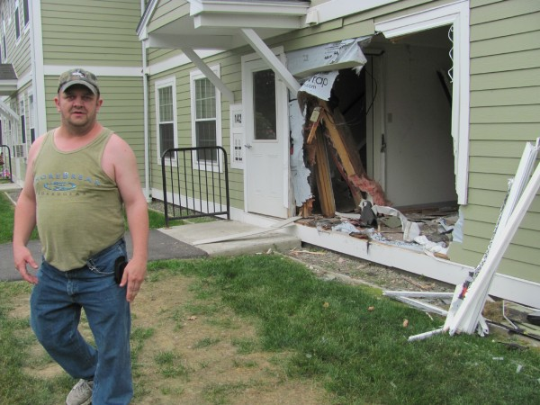 Joseph Sanborn walks out through a hole that was torn in his home at 104 Somerset Ave. on Friday when a motorist crashed through the wall. No one was injured.