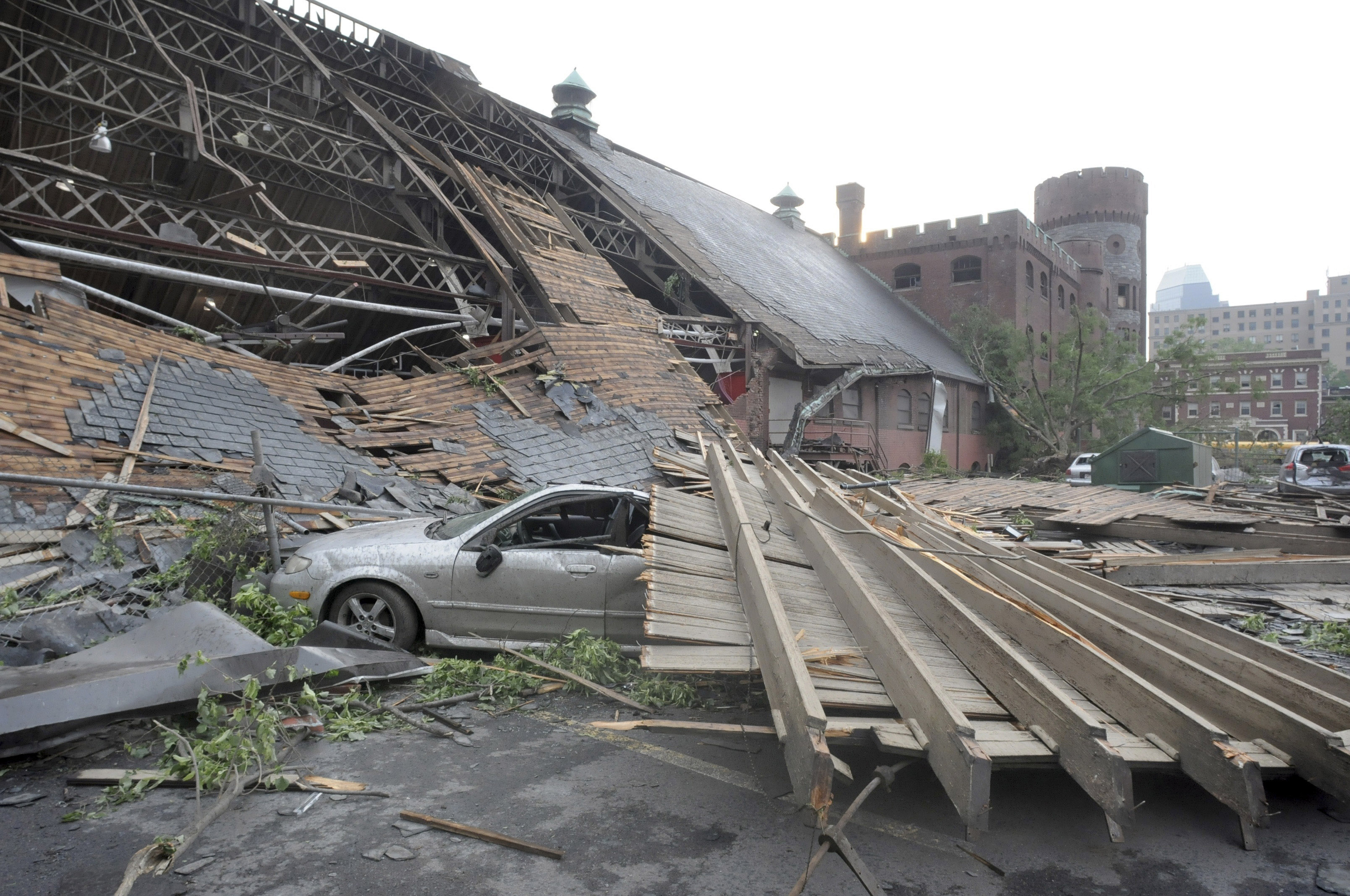A smashed car sits next to the South End Community Center, which lost most of its roof in a tornado that touched down in Springfield, Mass., Wednesday, June 1, 2011.