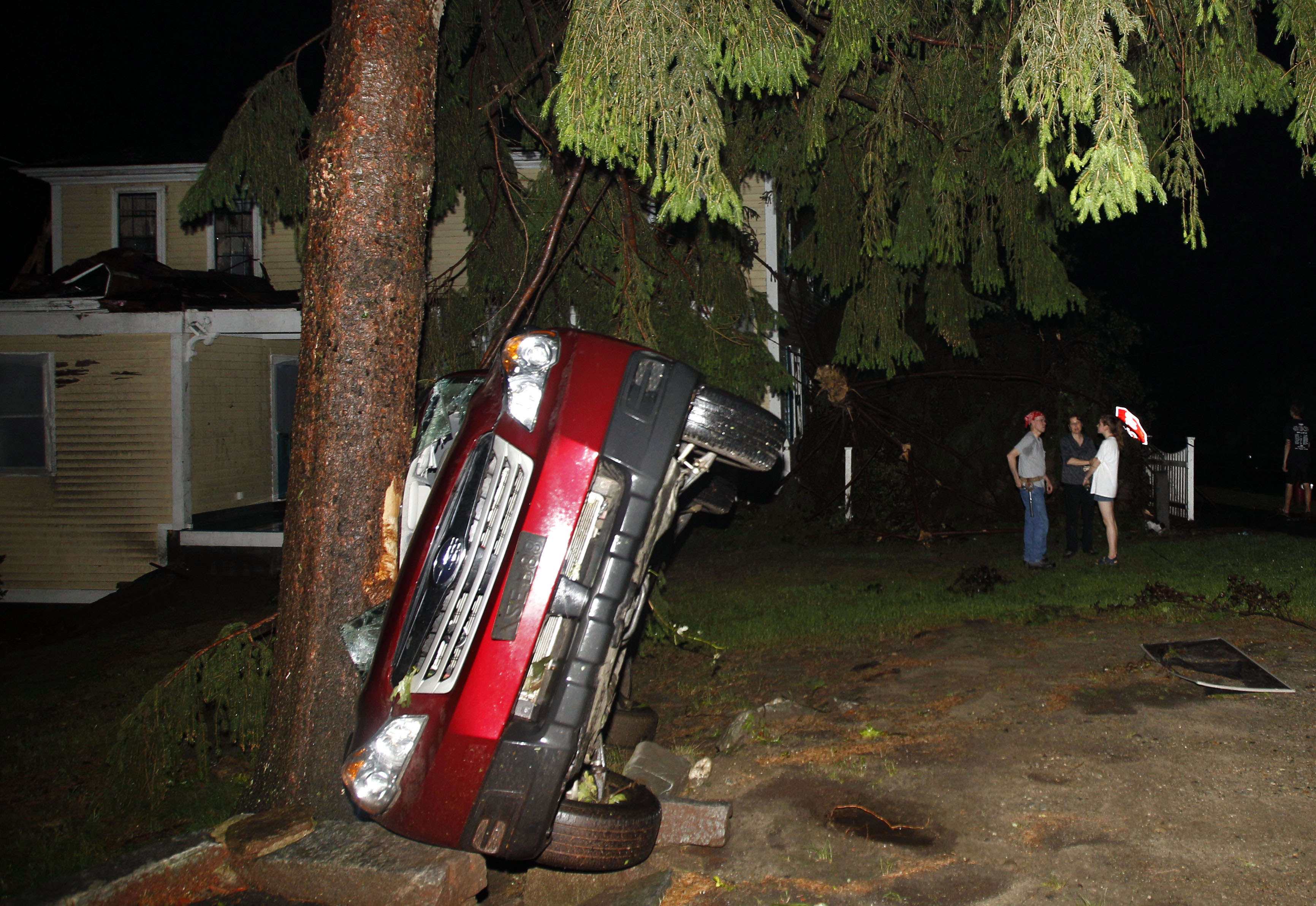 Residents gather in front of a house where a car lay smashed against a tree after a tornado swept through Monson, Mass. Wednesday, June 1, 2011.