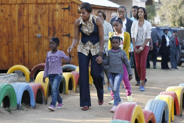 First lady Michelle Obama walks with children as she visits the Emthonjeni Community Center in Zandspruit Township, Johannesburg, South Africa, Tuesday, June 21, 2011. Also seen at rear are daughters Sasha and Malia Obama, mother Marian Robinson, niece Leslie Robinson and nephew Avery Robinson.